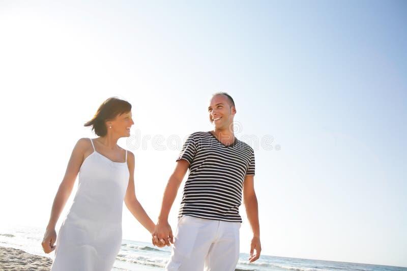 Pares jovenes felices que toman una caminata en la playa. fotos de archivo