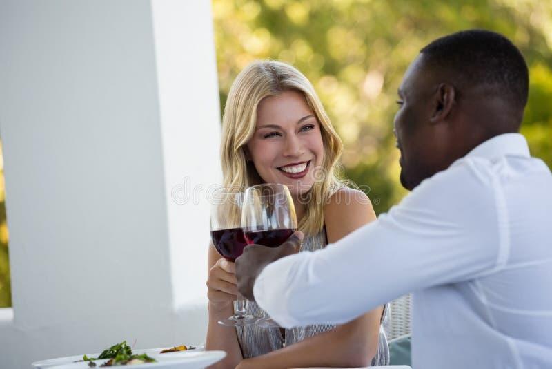 Pares jovenes felices que tuestan las copas en el restaurante fotos de archivo libres de regalías