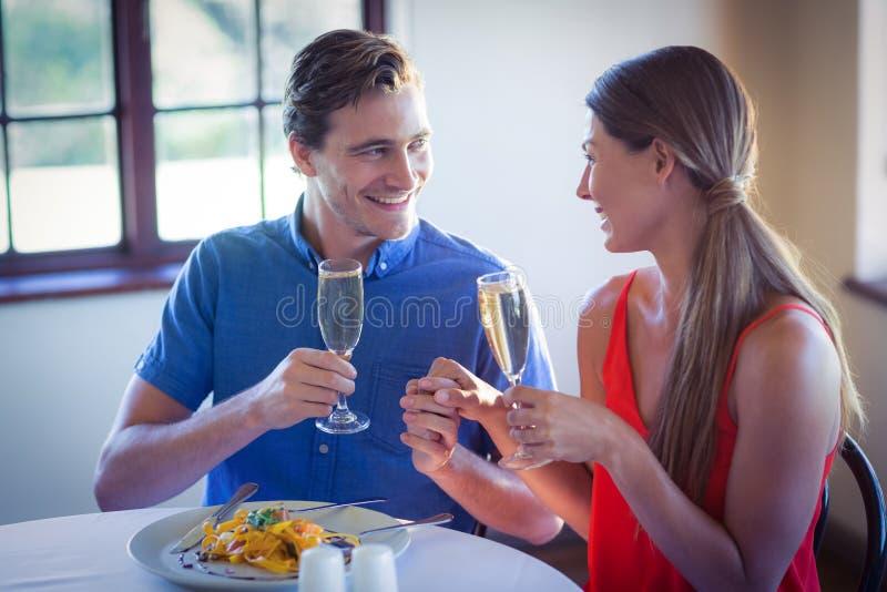 Pares jovenes felices que tuestan las flautas de champán mientras que almorzando foto de archivo