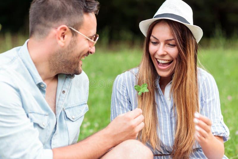 Pares jovenes felices sonrientes que pasan el tiempo junto en una comida campestre en parque foto de archivo libre de regalías