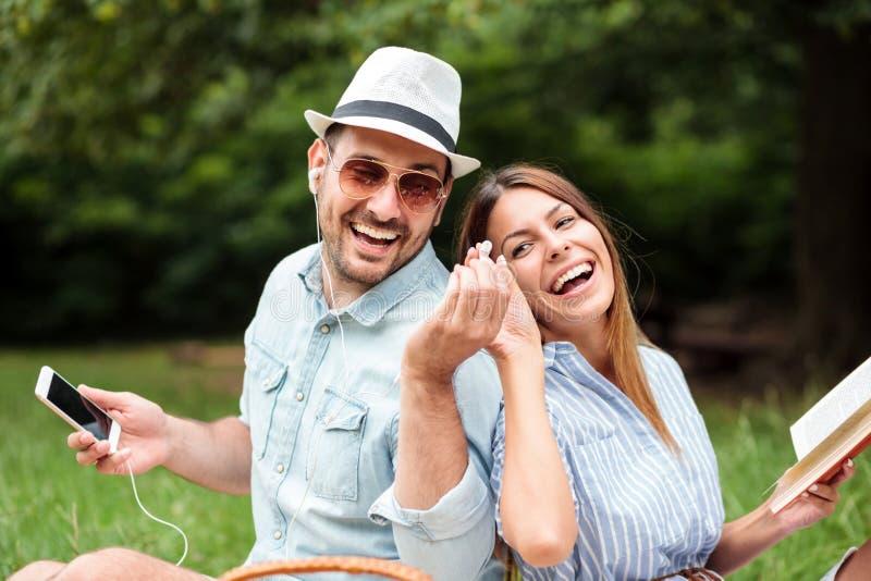 Pares jovenes felices sonrientes que tienen un gran rato en una comida campestre imagenes de archivo
