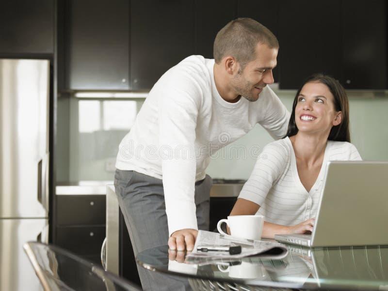 Pares jovenes felices usando el ordenador portátil imágenes de archivo libres de regalías