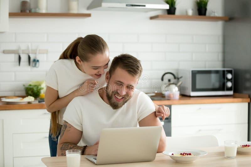 Pares jovenes felices usando el ordenador portátil junto en la cocina imágenes de archivo libres de regalías