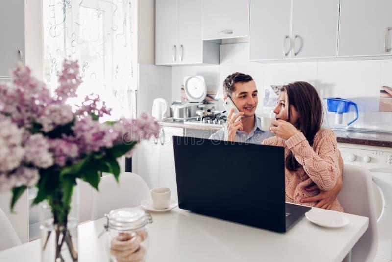 Pares jovenes felices usando el ordenador portátil mientras que desayunando en cocina moderna Hombre joven que habla en el teléfo foto de archivo