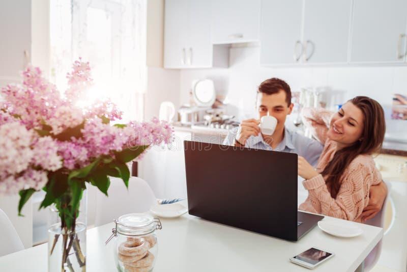 Pares jovenes felices usando el ordenador portátil mientras que desayunando en cocina moderna El hombre joven y la mujer beben el foto de archivo