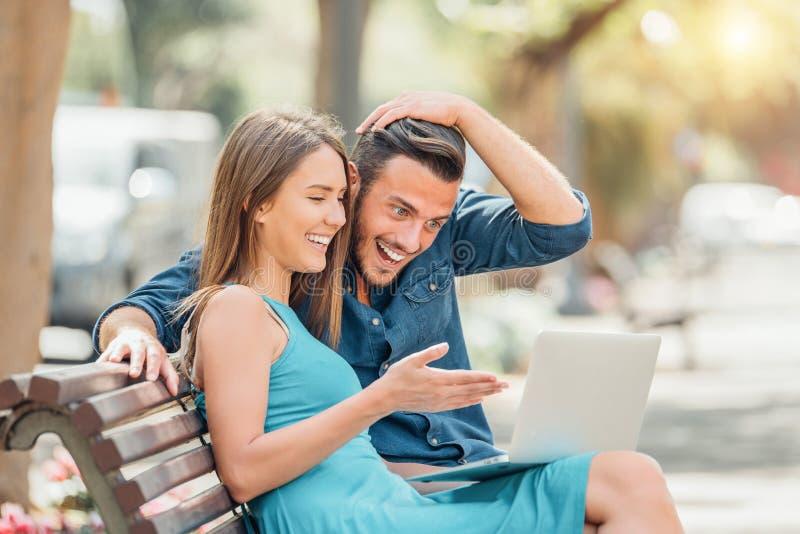 Pares jovenes felices usando el ordenador port?til que se sienta en banco en la ciudad al aire libre fotografía de archivo