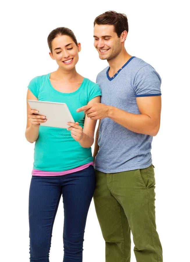 Pares jovenes felices usando la tableta fotos de archivo