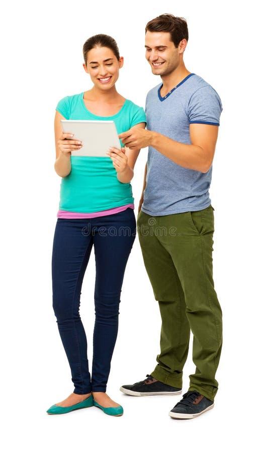 Pares jovenes felices usando la tableta de Digitaces imagen de archivo