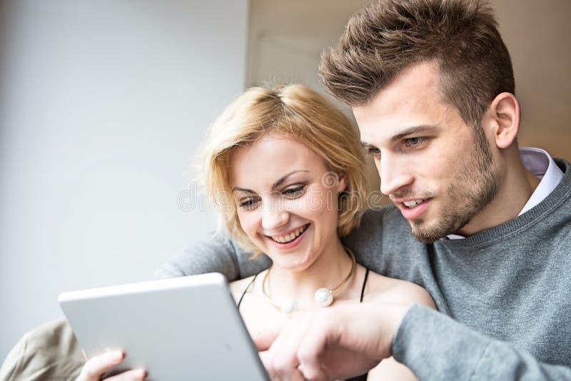 Pares jovenes felices usando la tableta digital en café imagen de archivo