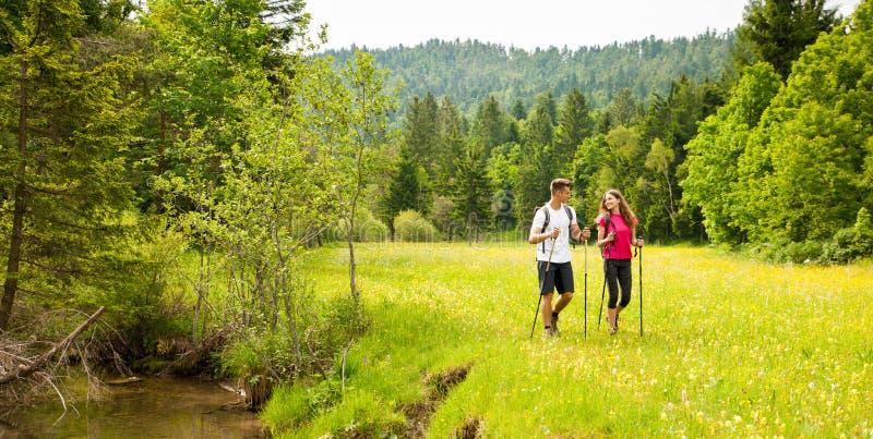 Pares jovenes hermosos activos que caminan la colina que sube de la naturaleza del ina o foto de archivo