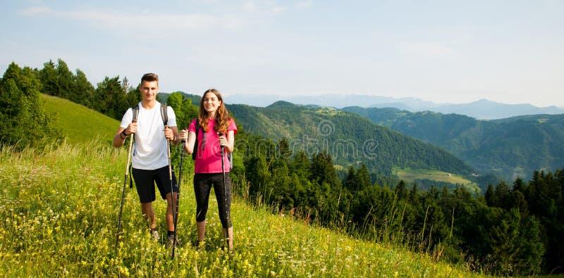 Pares jovenes hermosos activos que caminan la colina que sube de la naturaleza del ina o fotografía de archivo libre de regalías