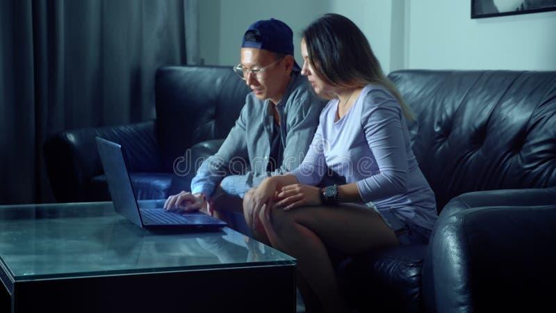 Pares jovenes hermosos asiáticos que se sientan en el sofá con la tableta en el cuarto por la tarde foto de archivo