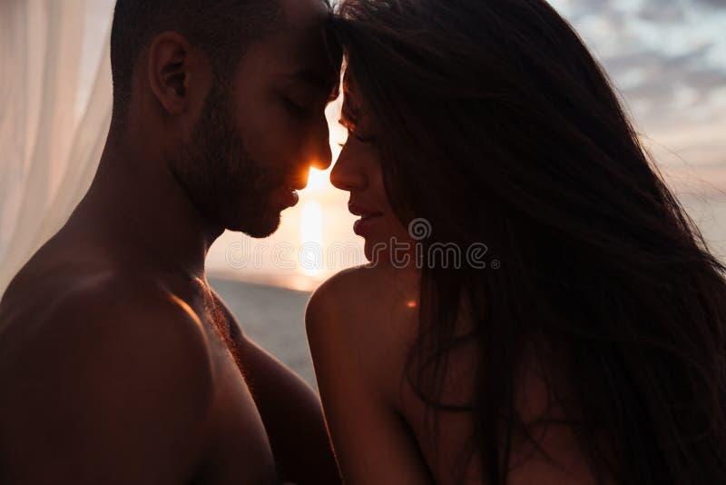 Pares jovenes hermosos blandos en puesta del sol foto de archivo libre de regalías
