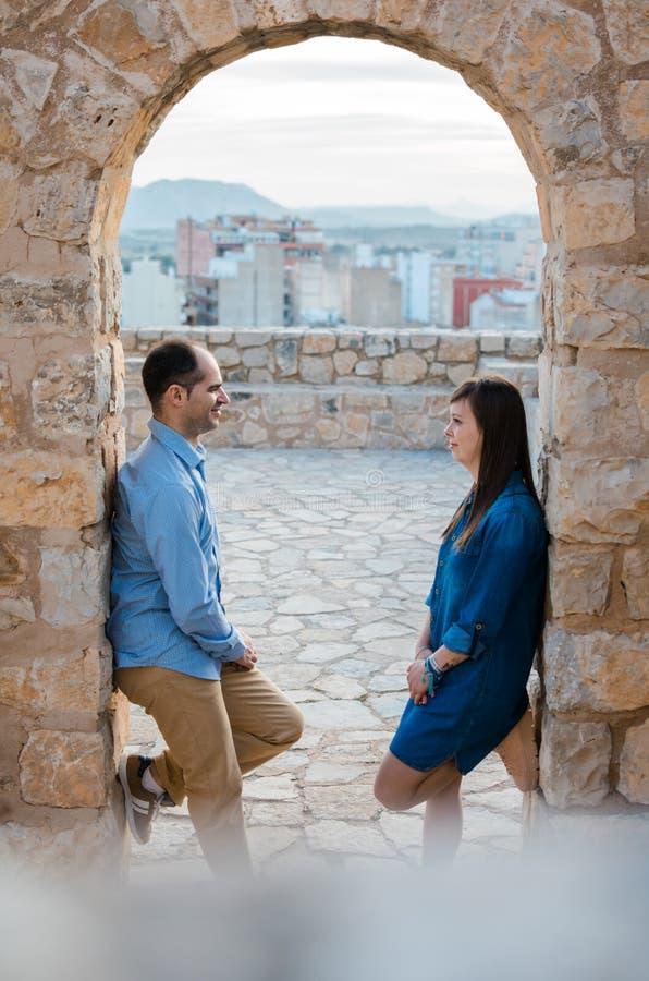 Pares jovenes hermosos cerca de las paredes antiguas del castillo viejo fotos de archivo libres de regalías