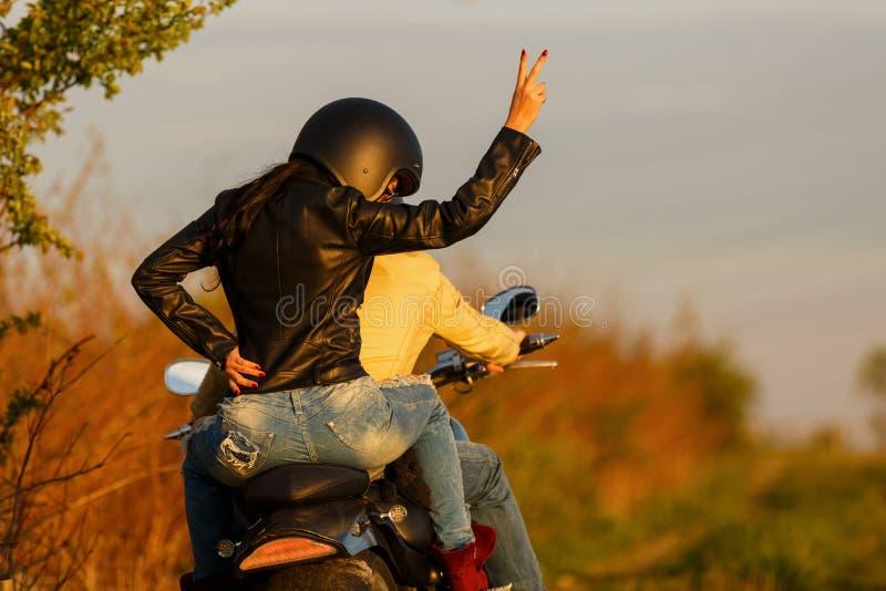 Pares jovenes hermosos con una motocicleta fotografía de archivo