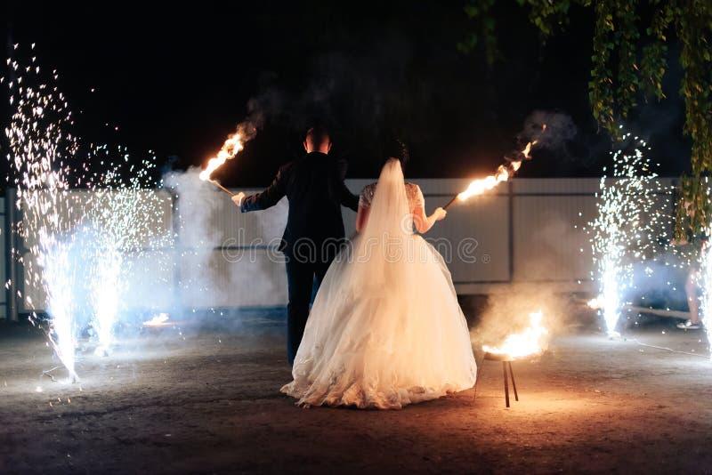 Pares jovenes hermosos del recién casado con las antorchas del fuego en sus manos y fuegos artificiales 1 fotos de archivo