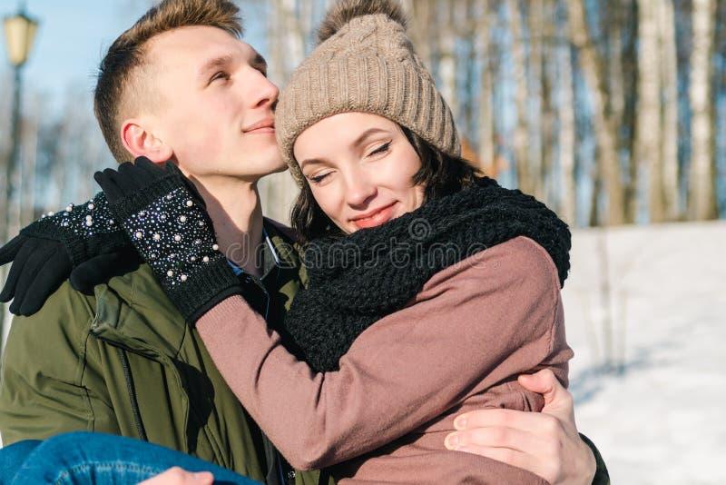 Pares jovenes hermosos en amor en el parque en un día de invierno soleado claro El hombre joven detiene a su novia imagen de archivo libre de regalías