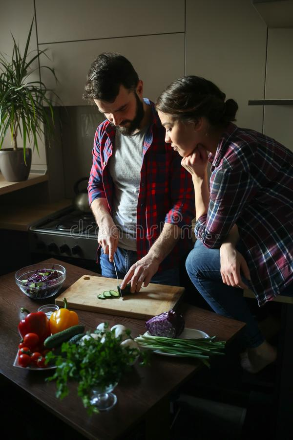 Pares jovenes hermosos en cocina en casa mientras que cocina la comida sana El hombre es ensalada de los cortes La mujer se sient imagen de archivo