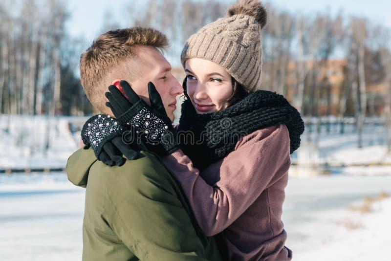 Pares jovenes hermosos en el amor que abraza en el parque en un día de invierno soleado claro imagen de archivo