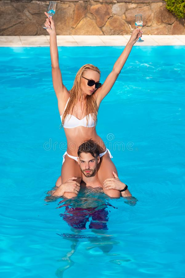 Pares jovenes hermosos en el amor que se relaja en silla de playa con el c?ctel E Maldivas o Miami imagenes de archivo