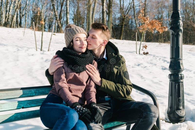 Pares jovenes hermosos en el amor que se sienta en un banco de parque en un día de invierno soleado claro Abrazos del muchacho y  foto de archivo