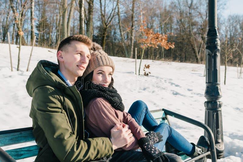 Pares jovenes hermosos en el amor que se sienta en un banco de parque en un día soleado claro El muchacho y la muchacha disfrutan imagen de archivo libre de regalías