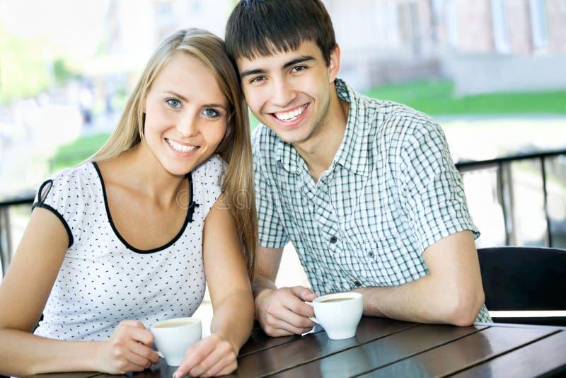 Pares jovenes hermosos en el café imagen de archivo libre de regalías