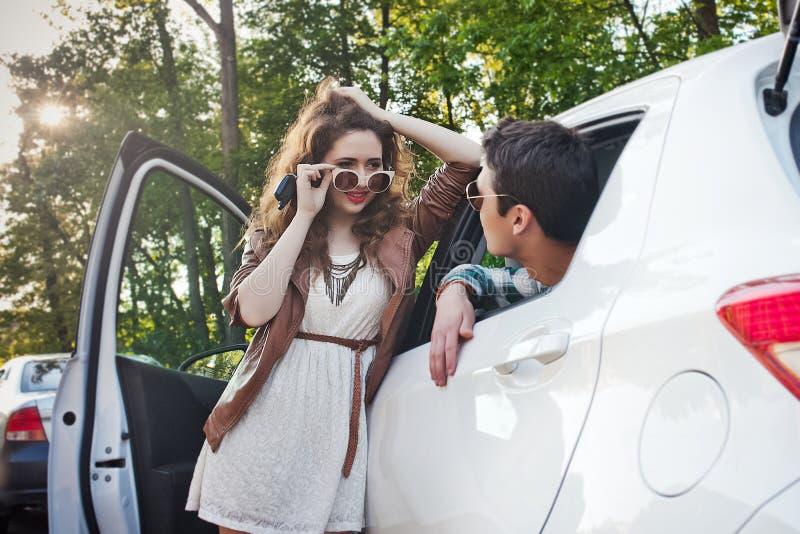 Pares jovenes hermosos en la naturaleza cerca del coche que tiene el ligón imagenes de archivo