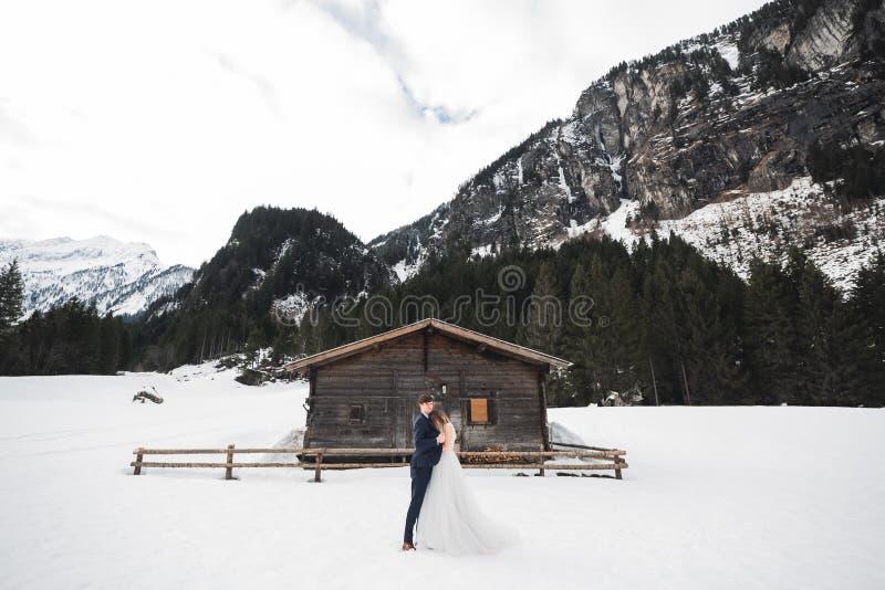 Pares jovenes hermosos en montañas del invierno Paseo del invierno de amantes Hombre que abraza a la mujer foto de archivo