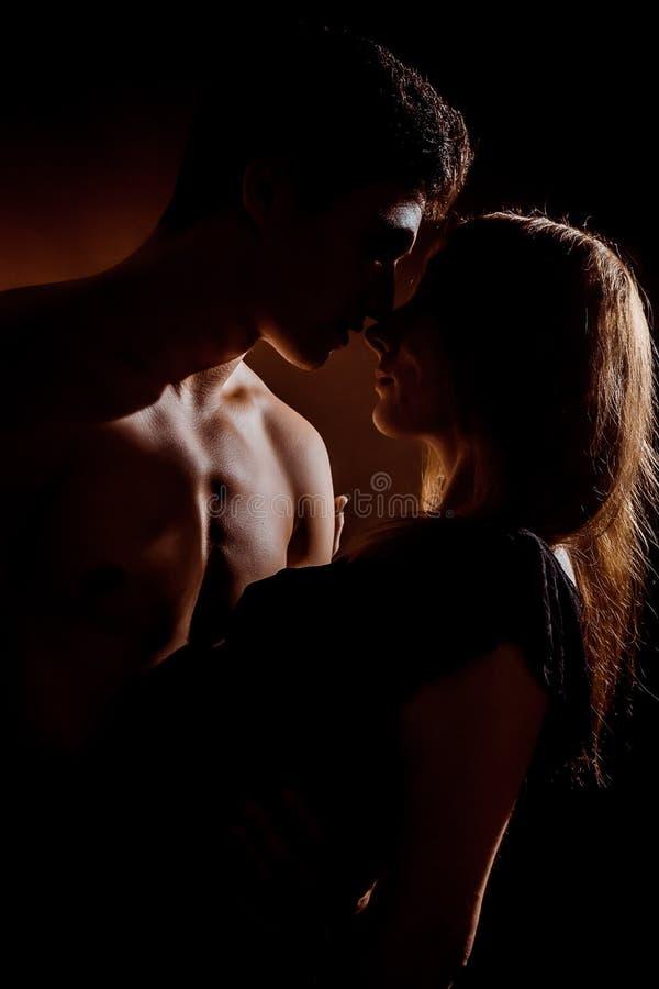 Pares jovenes hermosos que abrazan y que se besan aislados en fondo negro fotos de archivo libres de regalías