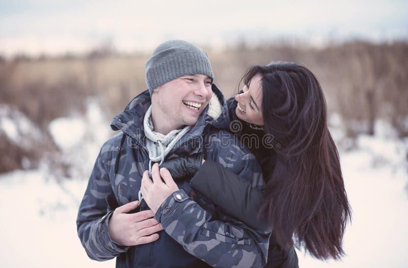 Pares jovenes hermosos que abrazan y que sonríen en parque del invierno Familia feliz imagenes de archivo