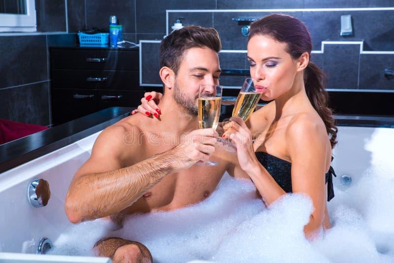 Pares jovenes hermosos que beben Champán en Whirlpool imagenes de archivo