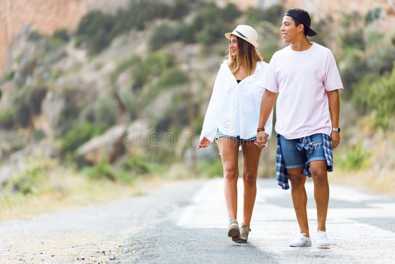 Pares jovenes hermosos que caminan en la montaña imagen de archivo