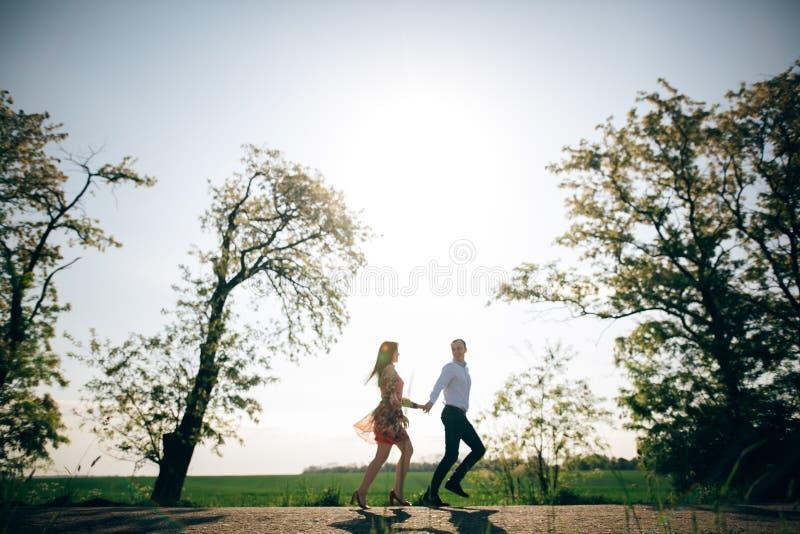 Pares jovenes hermosos que celebran las manos y el funcionamiento en sol en campo y árboles de la primavera Siluetas de la famili fotos de archivo