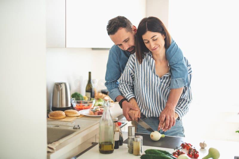Pares jovenes hermosos que cocinan junto en casa foto de archivo libre de regalías