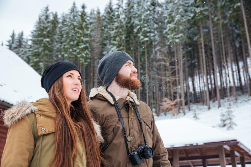 Pares jovenes hermosos que colocan y que gozan del bosque del invierno imagen de archivo libre de regalías