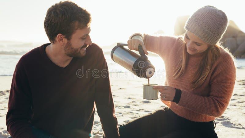 Pares jovenes hermosos que comen café en la playa fotos de archivo libres de regalías