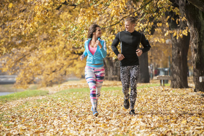 Pares jovenes hermosos que corren junto en el parque foto de archivo libre de regalías