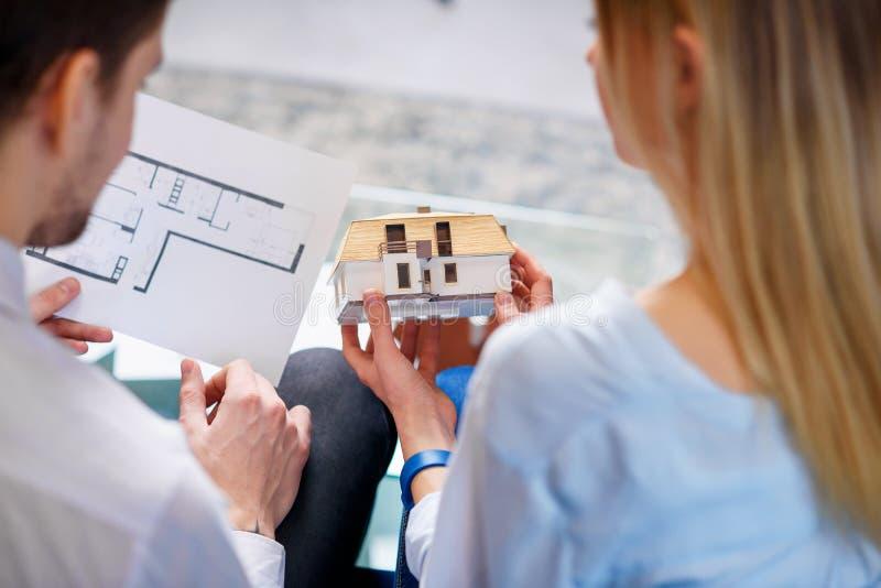 Pares jovenes hermosos que discuten el modelo 3d y el bosquejo de la casa futura imagenes de archivo