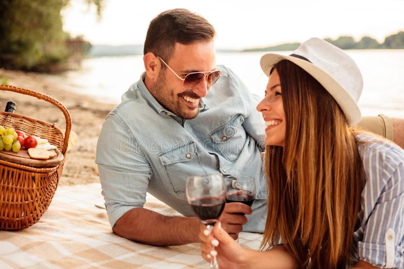 Pares jovenes hermosos que disfrutan de comida campestre en una playa imagen de archivo