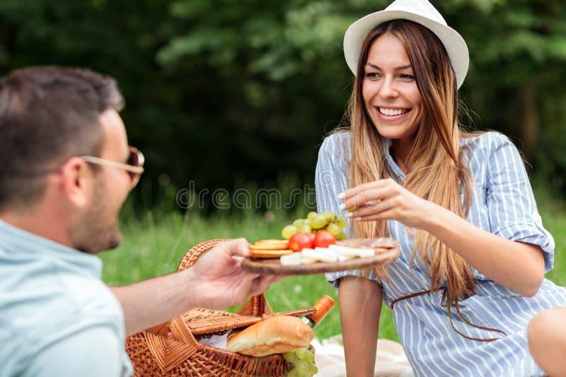 Pares jovenes hermosos que disfrutan de comida campestre rom?ntica en un parque foto de archivo libre de regalías