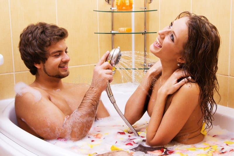Pares jovenes hermosos que disfrutan de un baño foto de archivo libre de regalías