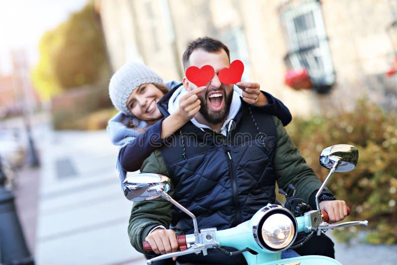 Pares jovenes hermosos que llevan a cabo corazones mientras que monta la vespa en ciudad en otoño imagenes de archivo