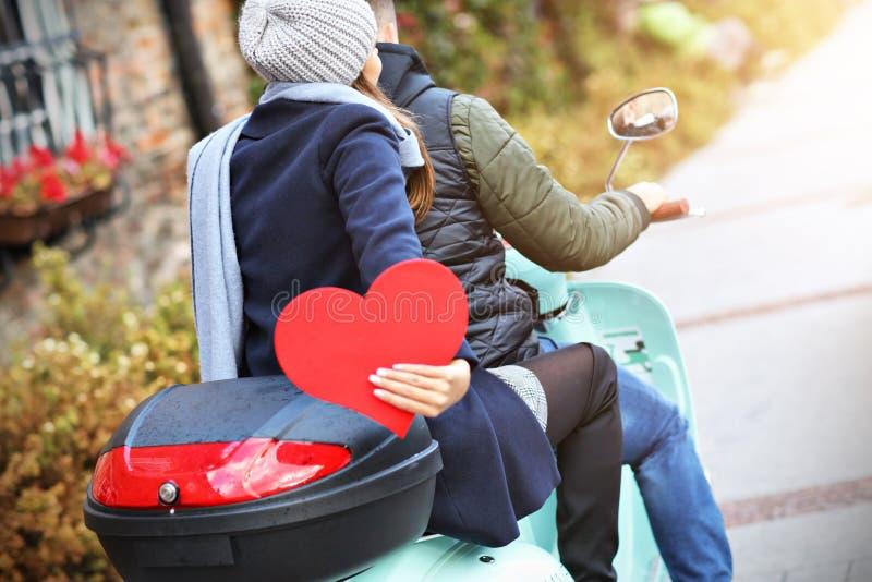 Pares jovenes hermosos que llevan a cabo corazones mientras que monta la vespa en ciudad en otoño imagen de archivo