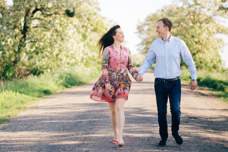 Pares jovenes hermosos que llevan a cabo las manos y que caminan en el camino en sol entre campo y árboles de la primavera Famili fotos de archivo
