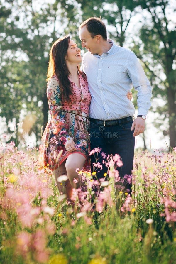 Pares jovenes hermosos que llevan a cabo las manos y que caminan en sol en prado de la primavera con las flores rosadas Familia f fotografía de archivo libre de regalías