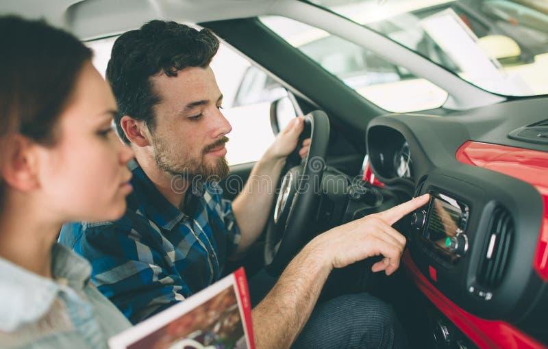 Pares jovenes hermosos que se colocan en la representación que elige el coche para comprar fotografía de archivo