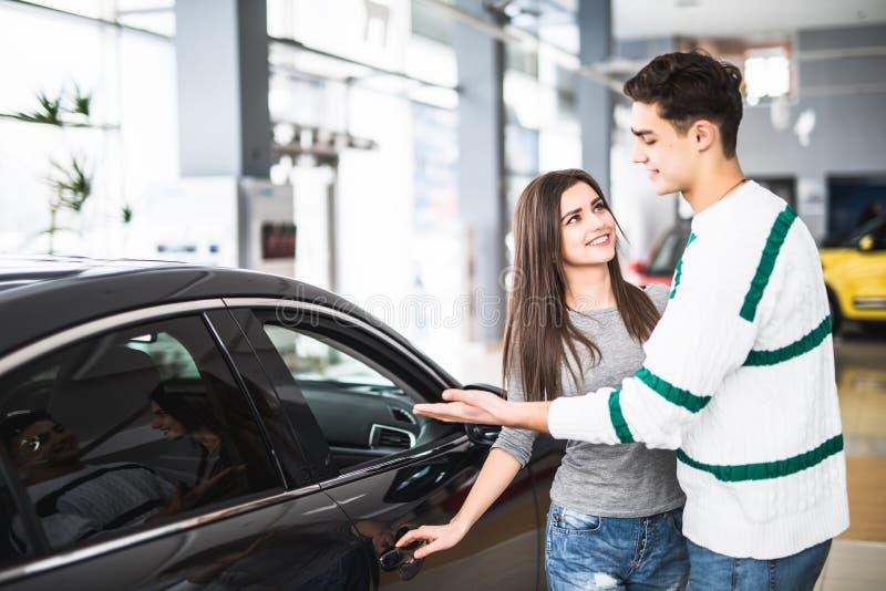 Pares jovenes hermosos que se colocan en la representación que elige el coche para comprar fotos de archivo libres de regalías