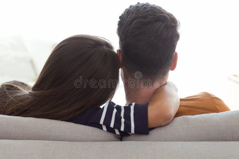 Pares jovenes hermosos que se relajan en el sofá en casa foto de archivo libre de regalías