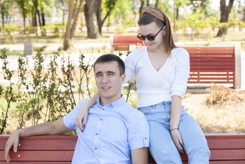 Pares jovenes hermosos que se sientan en un banco en el parque imágenes de archivo libres de regalías